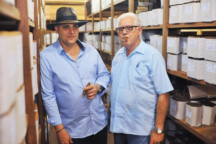 A.J. Fernandez and his father, Ismael, in the aging room, where cigars rest and blended tobaccos marry right after they are rolled. Ismael helps his son with the daily operations in the factory.