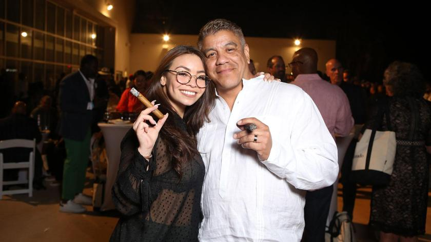 Vanessa Mota and Raymond Teixeira are all smiles with premium cigars in hand.