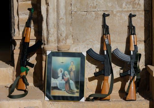 Waffen irakischer Soldaten, dazwischen ein Bild mit einem christlichen Motiv. (Bild: Hussein Malla / AP)