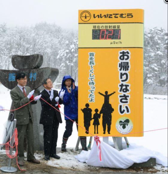 Figure 3. Réouverture du village d'Iitate. Les autorités accueillent les habitants sous un compteur affichant 0, 21 microsievert/h, avec l'interjection utilisée lorsqu'un membre de la famille rentre chez soi : « Bon retour ! » (Source de l'Image : Kyodo News)