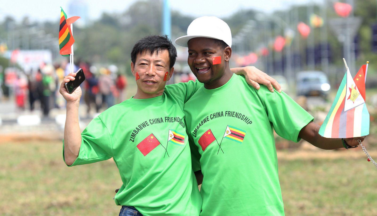 Un ressortissant chinois anonyme et un homme zimbabwéen s'enlacent  en accueillant le président chinois Xi Jinping à son arrivée à Harare, au Zimbabwe, le 1er décembre. 2015 (AP/Tsvangirayi Mukwazhi)