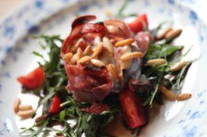 feige, mit ziegenkäse gefüllt und im schinkenmantel, auf rucola und tomaten aus dem garten