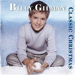 "Cover of Billy Gilman's album ""Classic Christmas,"" which depicts a young blond boy sitting in snow and making a snowball while smiling at the camera."