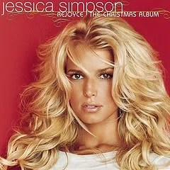 "Cover of Jessica Simpson's album ""Rejoyce: The Christmas Album,"" which depicts a tan white woman with blond hair staring at the camera in front of a red background."