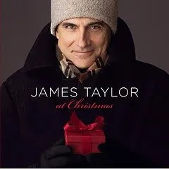 "Cover of James Taylor's album ""James Taylor at Christmas,"" which depicts Taylor standing in front of a plain wall while dressed in warm clothing and holding a wrapped box."