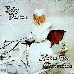 "Cover of Dolly Parton's album ""Home For Christmas,"" which depicts Parton, dressed in white, sitting in a sled in a snowy outdoor environment."