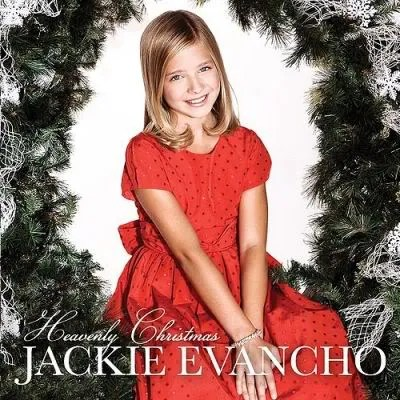 "Cover of Jackie Evancho's album ""Heavenly Christmas,"" depicting a young blond girl wearing a festive dress sitting beneath what appears to be a large wreath."