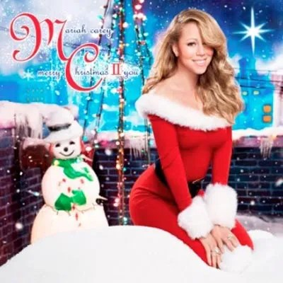 Cover of Mariah Carey's second (!!) Christmas album, which depicts Carey sitting in an outdoor environment amongst holiday decorations while wearing a red dress with white fur trim.