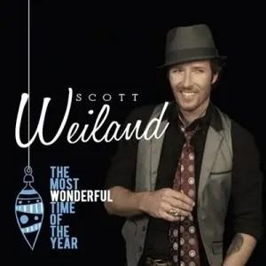 "Cover of Scott Weiland's album ""The Most Wonderful Time of the Year,"" depicting Weiland standing in front of a dark background while smiling and wearing a collared shirt, tie, vest and fedora."