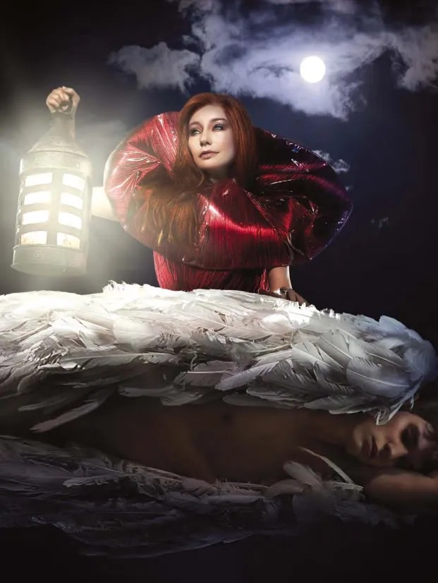 Image of Tori Amos, wearing some kind of very shiny red dress with a huge circular collar, leaning over a sleeping angel while hoisting a lantern