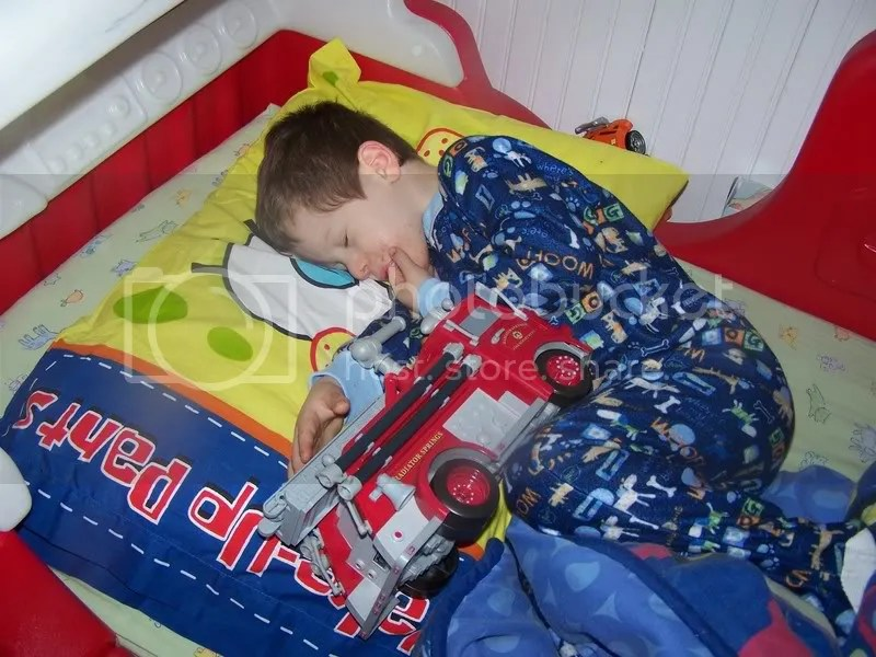 sleeping with his fire truck...in his fire truck bed