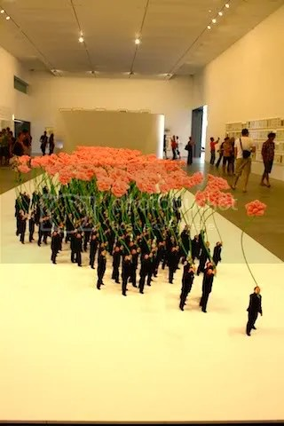Hundreds of soft little China men all holding a large flower.