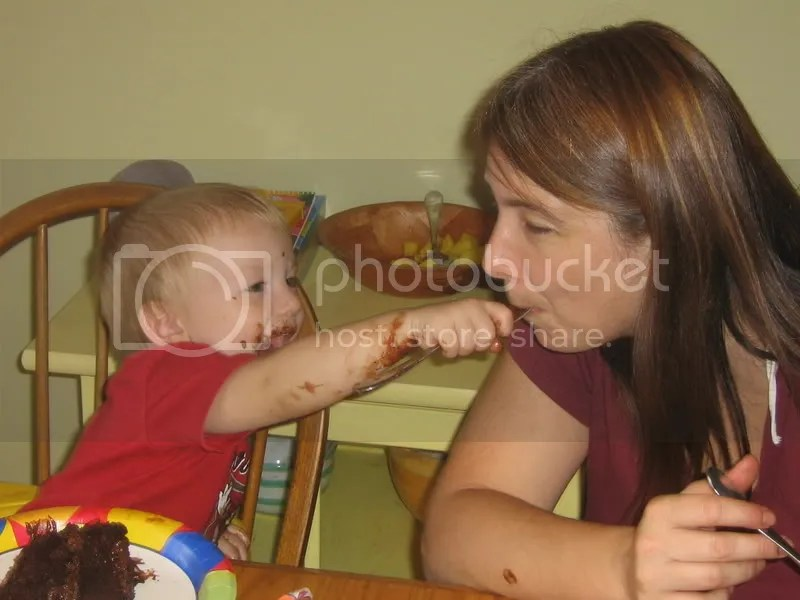 My son, at his 2nd birthday, covered in chocolate and joyfully feeding me chocolate cake
