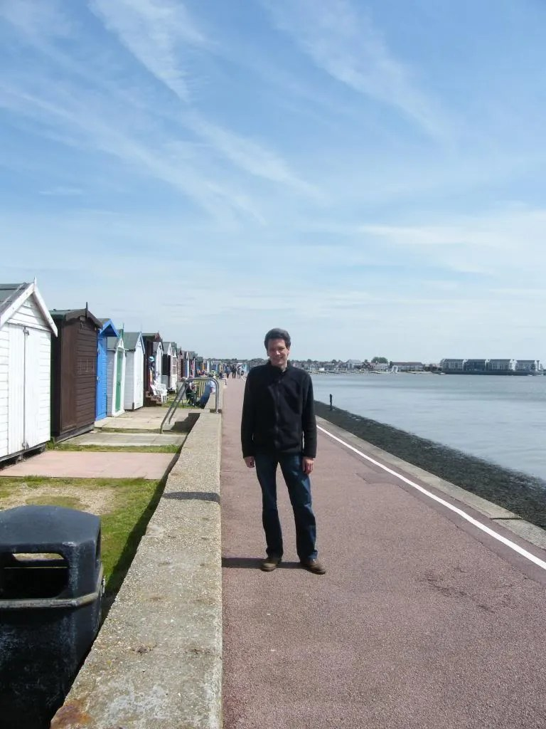 The photo shows a man facing the camera. The sea is on his left. On his right is a row of wooden beach huts in various colours
