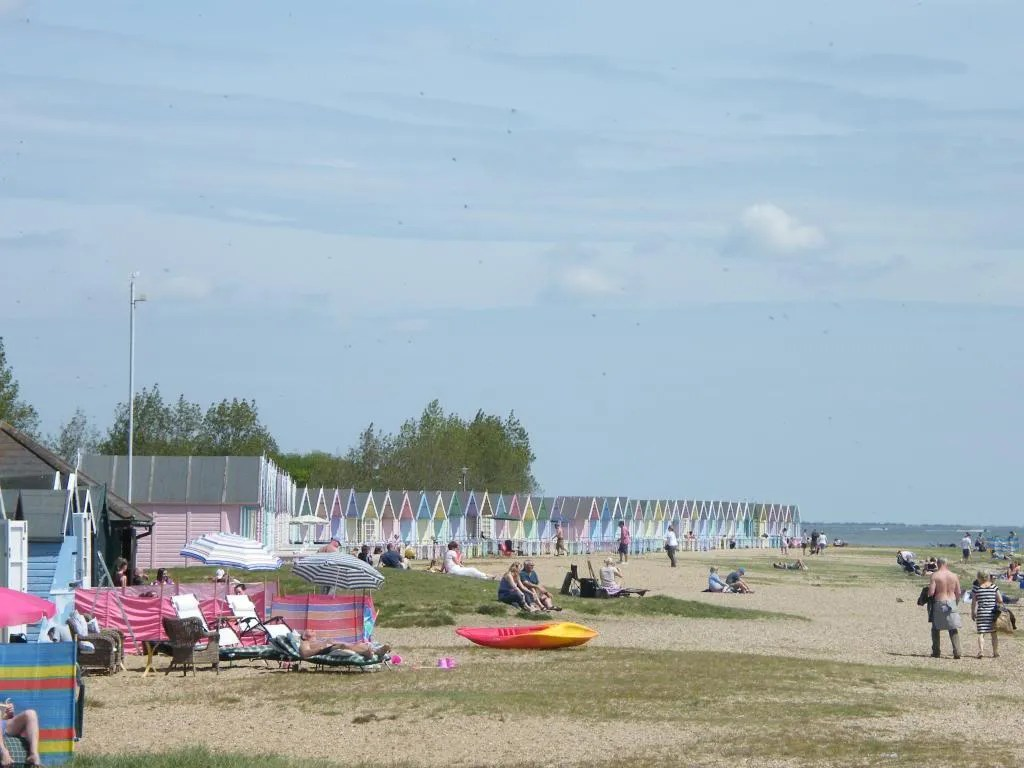 Mersea Island beach with pastel beach huts in the background