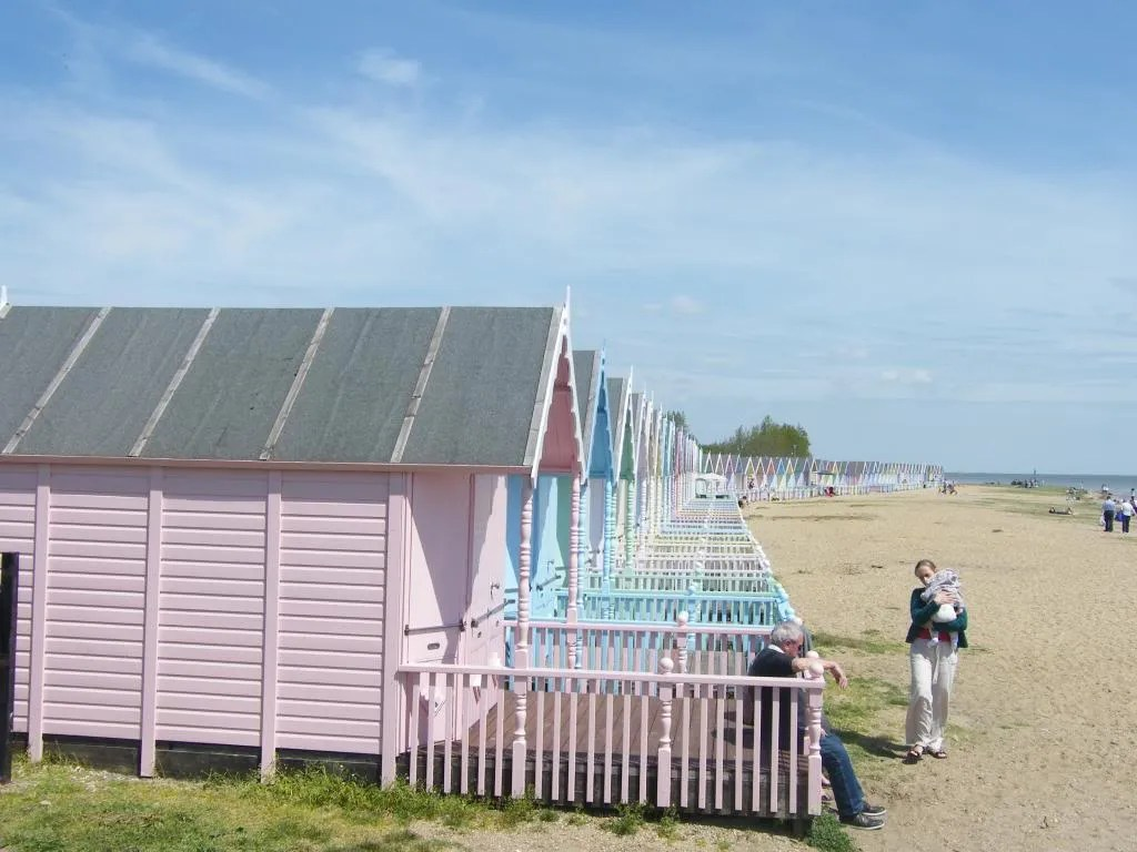 A pastel pink wooden beach hut with other pastel huts behind it