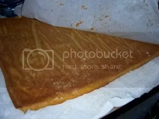 Flip the cake onto a clean towel immediately. Peel off the parchment paper and begin to roll the cake.
