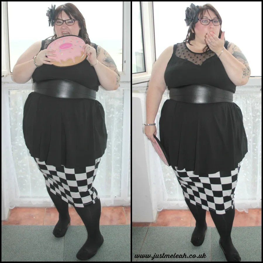 plus size outfit with black dress, leather belt, checkerboard print skirt, and donut clutch