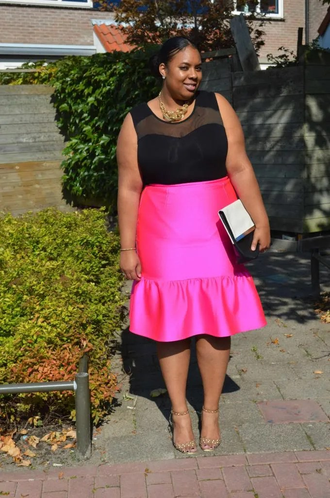 plus size outfit with sheer black top and metallic hot pink peplum skirt