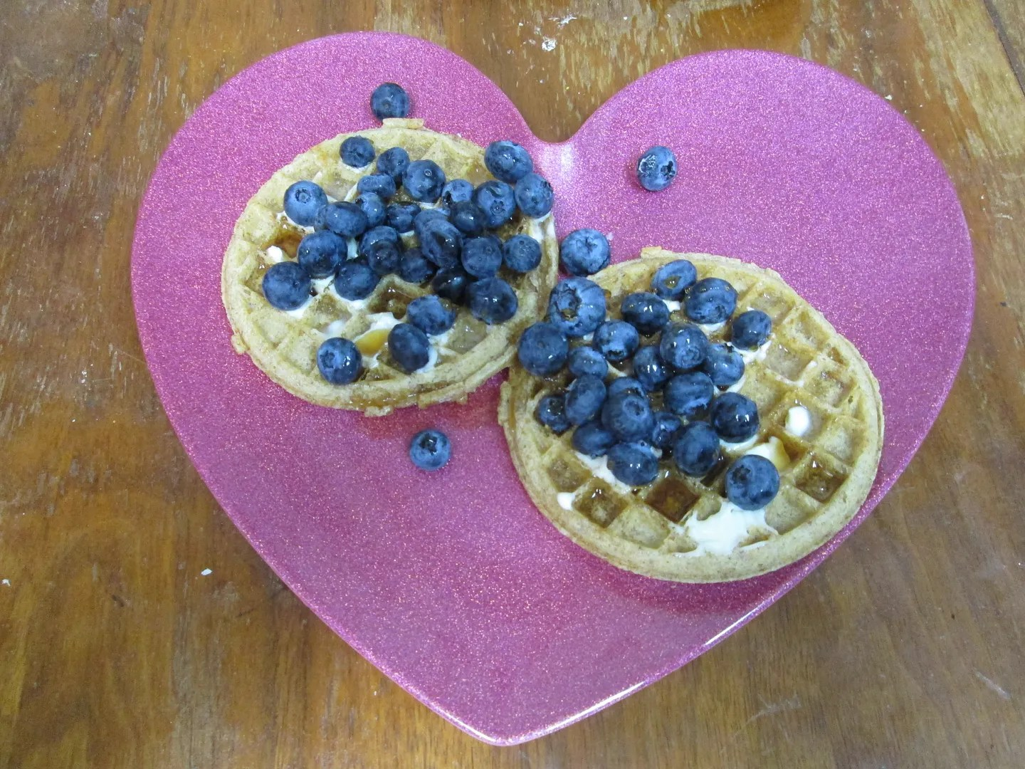 waffles with blueberries and maple syrup on pink sparkly heart-shaped plate