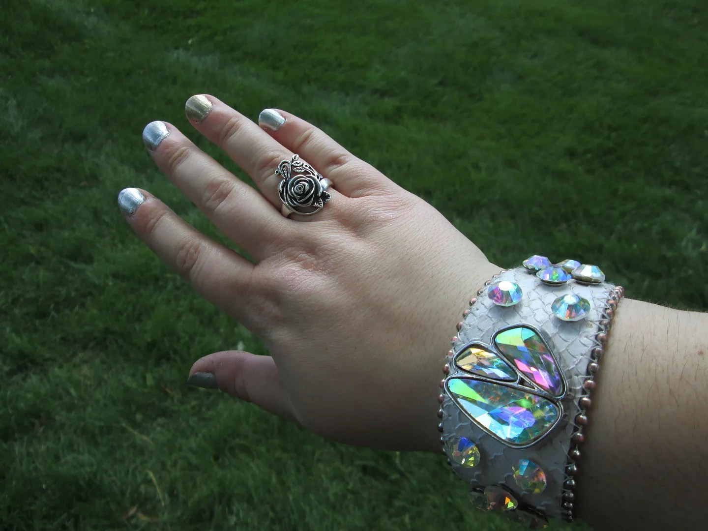 hand with gold and silver nail polish, rose ring, and rhinestone wristband