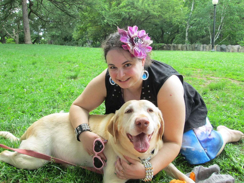 plus size woman cuddling a yellow labrador dog in a park