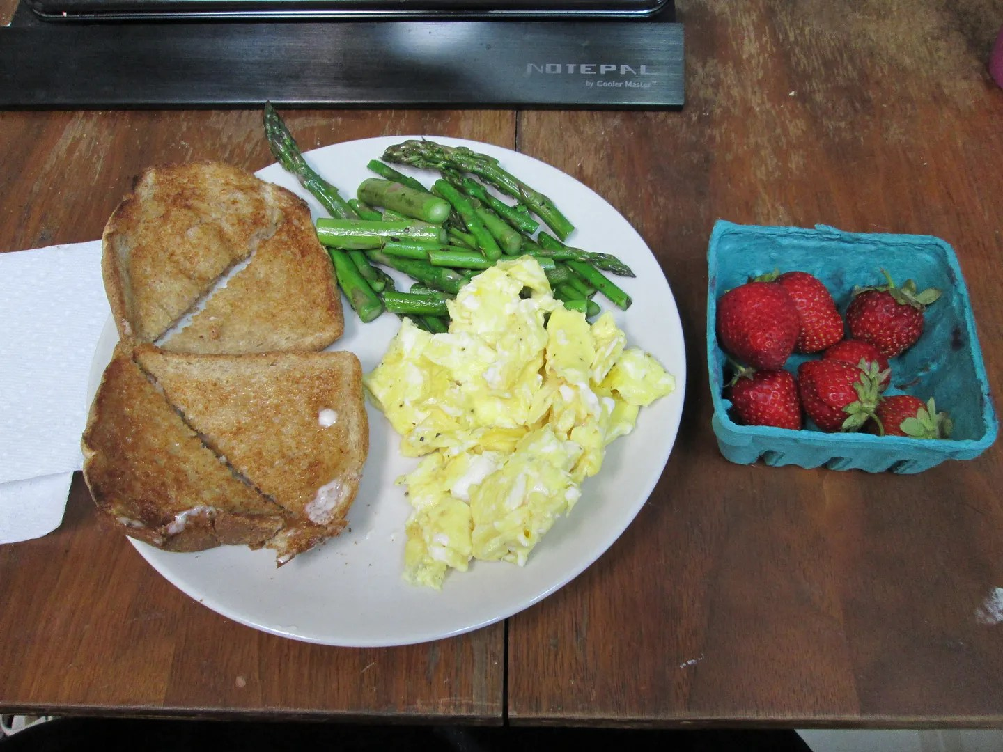 plate with toast, scrambled eggs, sauteed asparagus, next to container of strawberries