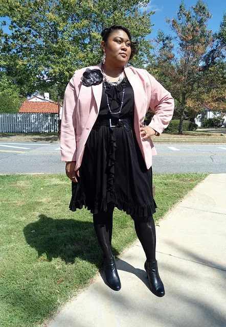 plus size woman wearing black dress with blush pink jacket and flower