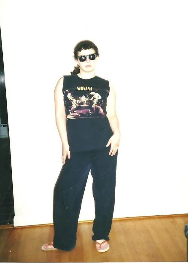 teenager in the 90s wearing all-black, nirvana shirt and pants, and sunglasses