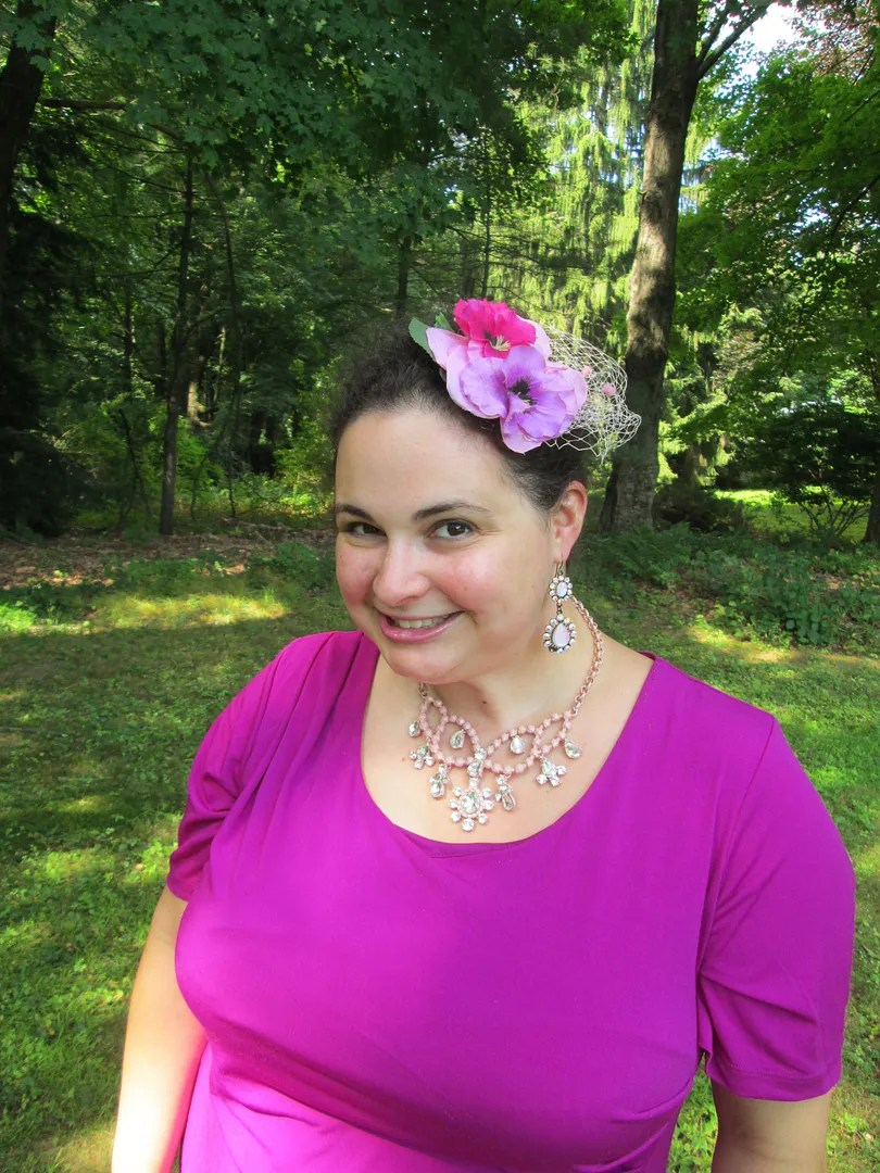 plus size outfit magenta dress, rhinestone necklace, and flower fascinator