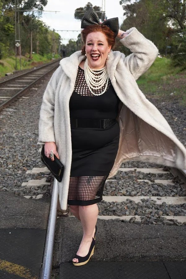 plus size outfit with black windowpane skirt and top, multi-strand pearl necklace, giant hair bow