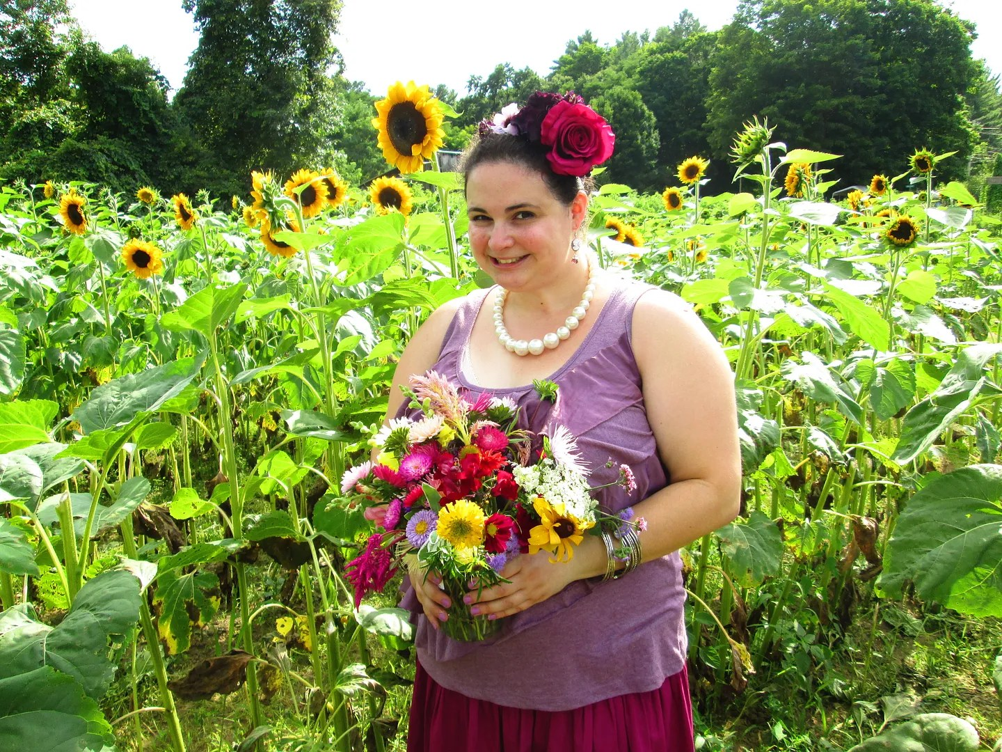 plus size outfit purple and burgundy standing in field of sunflowers