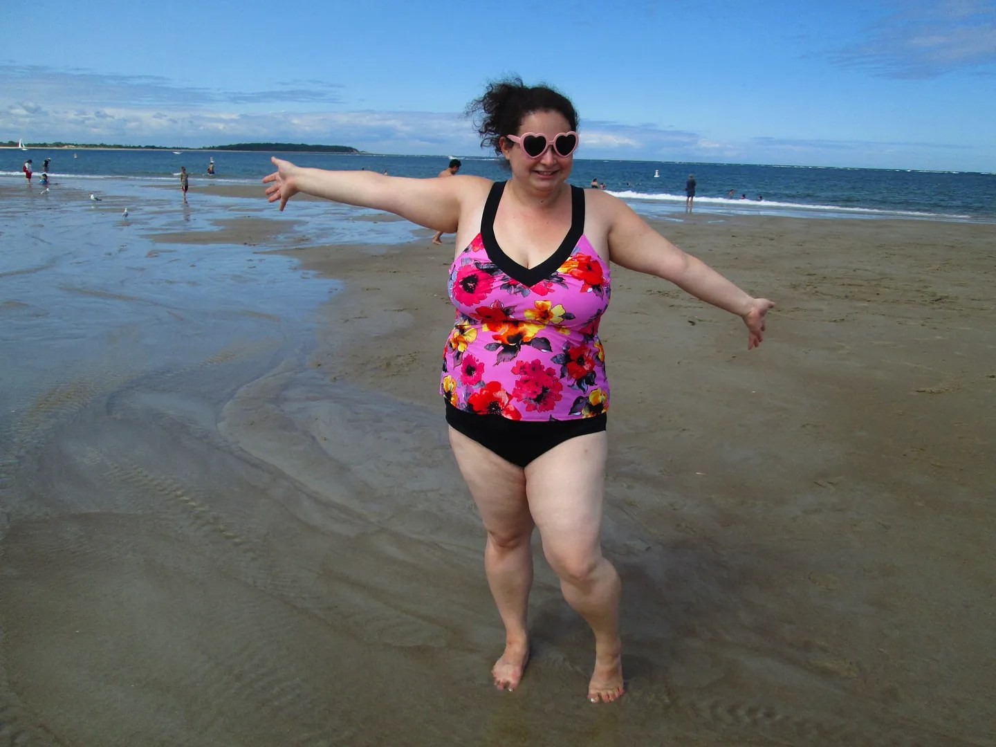 plus size woman on beach wearing pink floral tankini