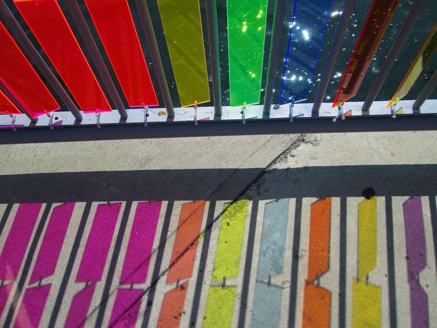 close-up of rainbow plexiglass panels and their reflections on the sidewalk