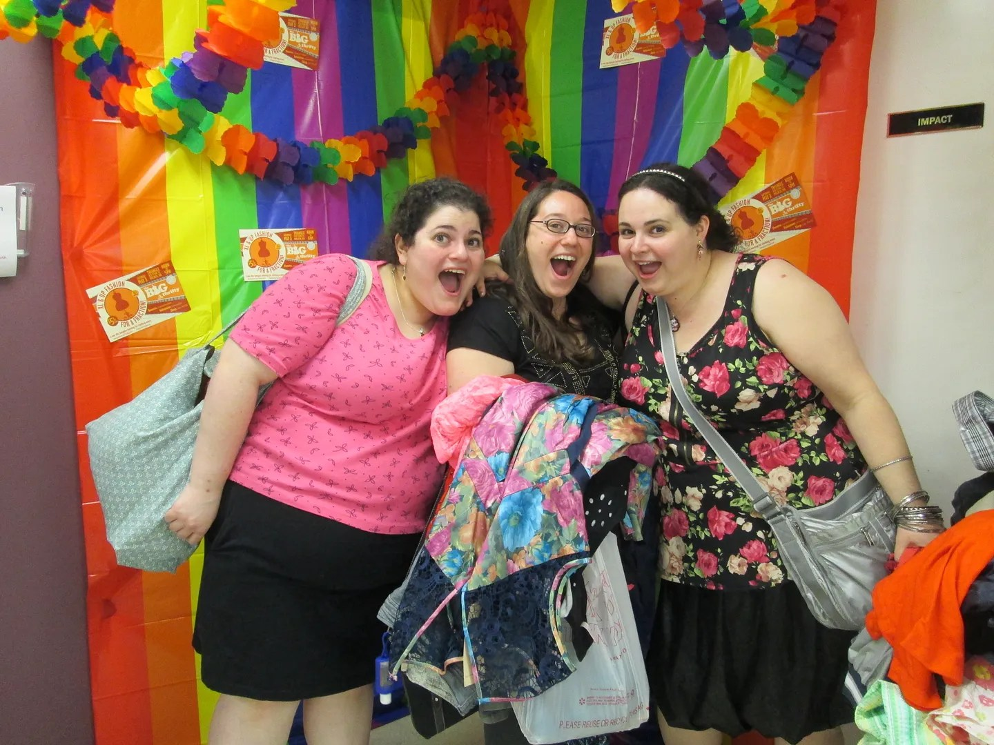 three women making silly faces in rainbow photobooth