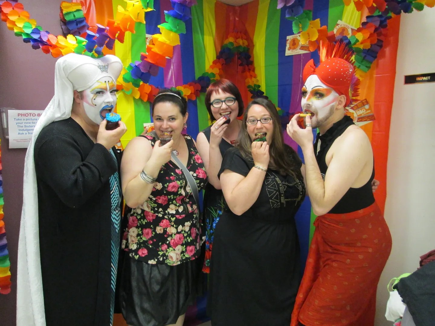 group of women and queer nuns eating cupcakes in rainbow photobooth