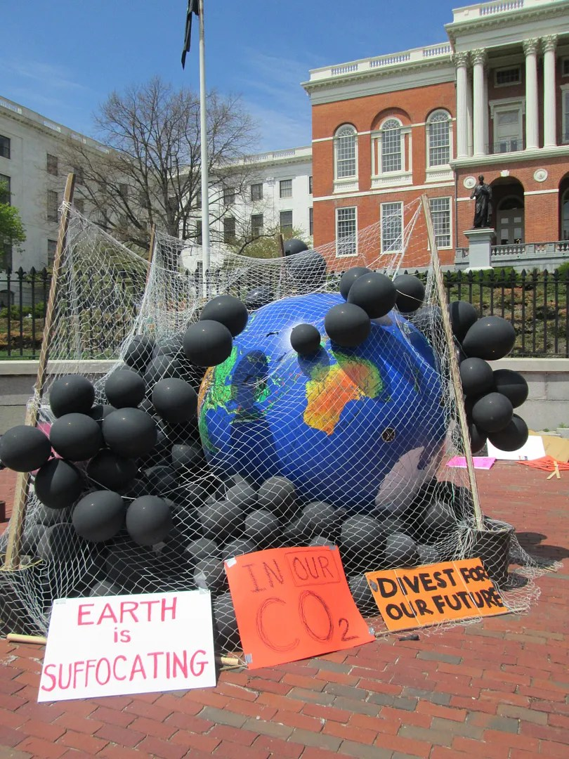 giant earth surrounded by black balloons representing carbon dioxide at fossil fuel divestment rally