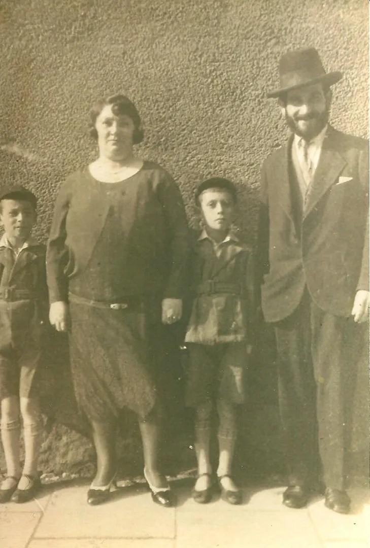 sepia-tinted black and white photo of a family from the 1930s: mother, father, and two boys