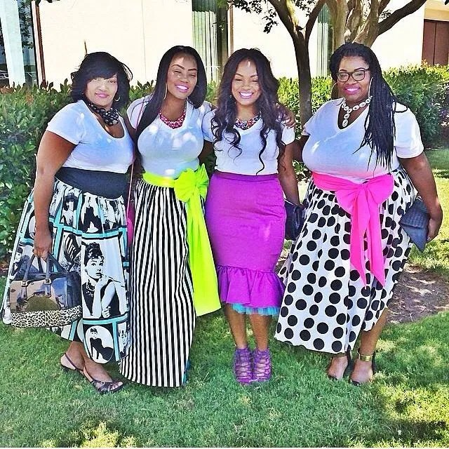 four plus size women friends wearing black and white outfits with pops of pink, yellow, and blue