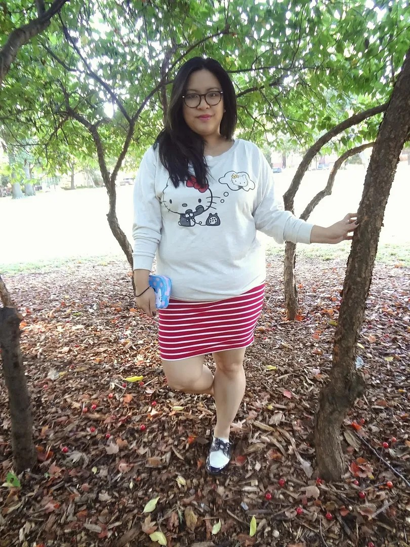 plus size outfit with white hello kitty sweatshirt and red and white striped skirt