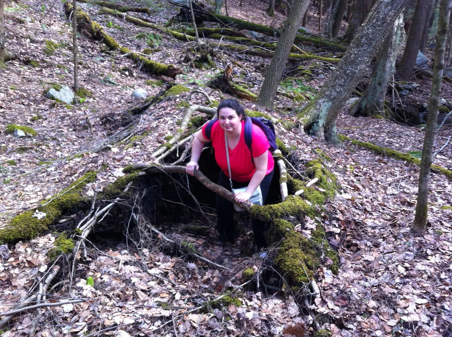 woman wearing hot pink shirt climbing out of tree roots in the woods