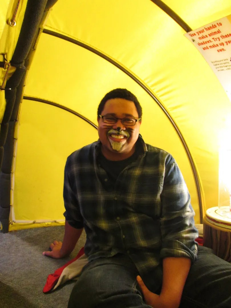 man wearing lion face paint, sitting in yellow tent