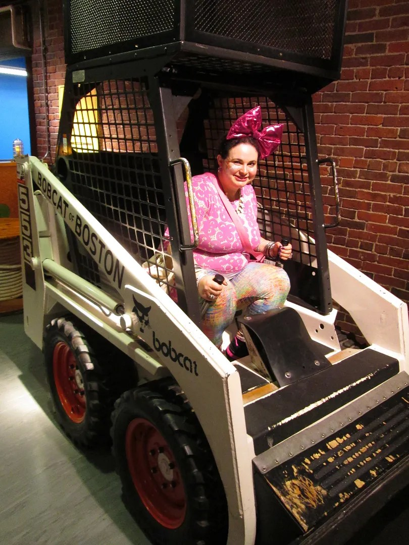 woman sitting in a construction bobcat in children's museum