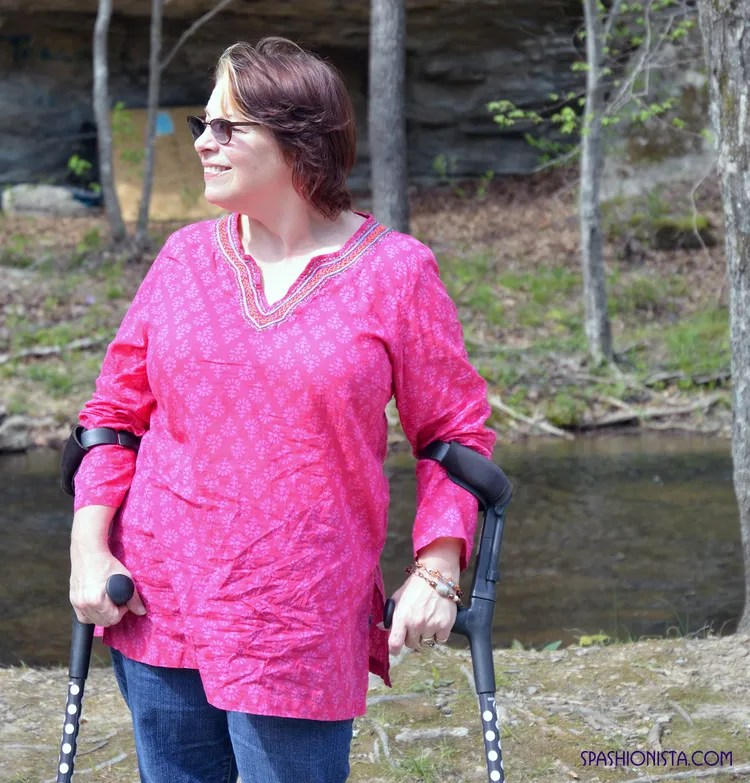woman using crutches wearing jeans and hot pink indian tunic