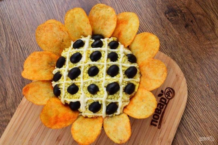 8. Перед подачей на верхний слой салата нанесите сетку майонеза, в ячейки – половинки маслин. По краям салат оформите крупными чипсами. Приятного аппетита!