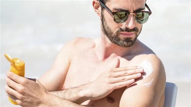 Un homme met de la crème solaire