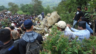 Rescuers and onlookers survey the crash site