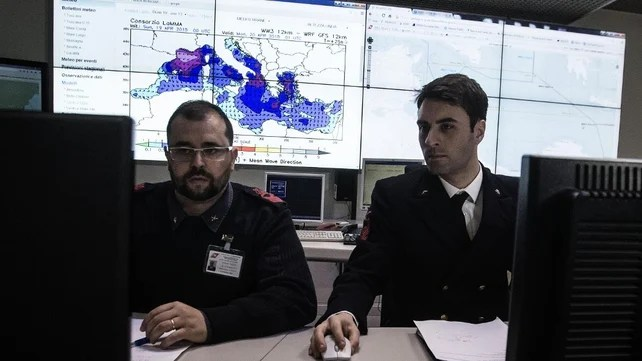 Personnel in the control room room of the Italian Coast Guard in Rome help coordinate relief efforts