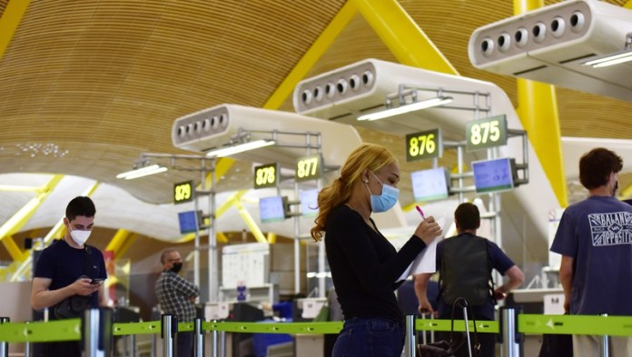 People check in at the Adolfo Suarez Madrid Barajas airport in Spain today after travel restrictions are lifted