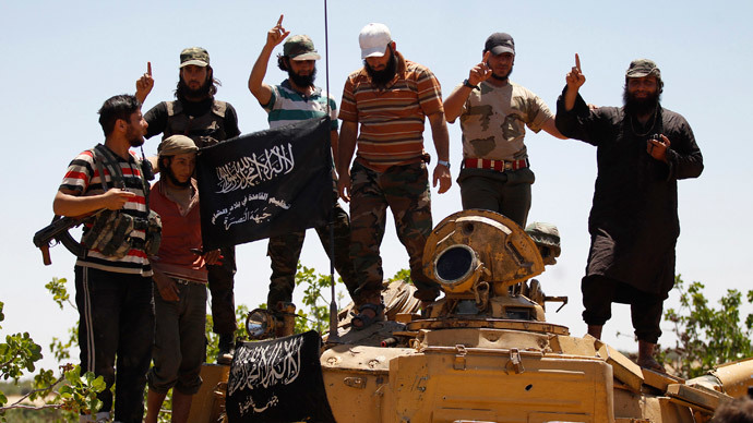 Islamist Syrian rebel group Jabhat al-Nusra members gesture while posing on a tank on Al-Khazan frontline of Khan Sheikhoun, northern Idlib province.( Reuters / Hamid Khatib)